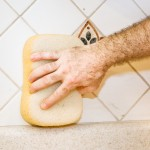 Worker's hand using a sponge to wipe fresh grout from ceramic tile